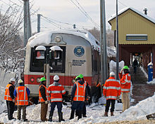 "Eight men wearing neon orange jackets or vests with reflective stripes and green or white hard hats, most with their backs to the camera, stand in a ragged row in snow across the bottom of the image. In front of them is the front of a gray rail passenger train with a wide red stripe around its lower section between two gray square metal columns that rise to the top of the image. The words ""Metro-North Commuter Railroad"" and the Connecticut state seal are visible on one side of the front.  Its roof is covered with snow. In the rear right is a dull yellow off-center snow-covered gabled canopy with the words ""New Canaan"" in the field sheltering a concrete platform."