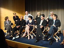 The cast seated in director's chairs