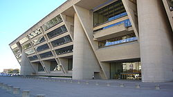 A tall beige building with an angled front face, leaning out from the top, is supported by three columns and covered with rows of windows