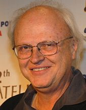 A profile image of Dennis Muren. A middle-aged, balding Caucasian male with short-white hair on the sides of his head. He is wearing dark glasses and looking towards the camera with a smile.