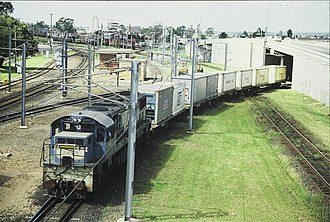 Queensland Railways 2470 class - 2493 hauls a short container train across the Standard Gauge line to Sydney at Yeerongpilly in 1987