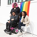 Disabled BIPOC in front of pride flag.jpg