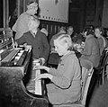 Een meisje speel piano, waaraan ook een jongen staat Op achtergrond eten mannen, Bestanddeelnr 255-9476.jpg