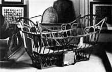 A basket made of iron bars sit among artefacts, such as plaques, portrait collages, and cannon.