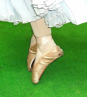 The ballet shoes of a dancer en pointe.