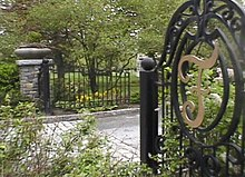 An open gate revealing the road to enter a cemetery, surrounded by grass, flowers and trees.