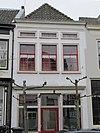 foto van Pand met verdieping, lage zolderverdieping en schilddak. Gepleisterde lijstgevel met geprofileerde omlijstingen van de vensters