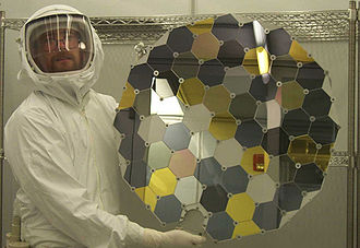 "Genesis (spacecraft) - A Genesis collector array in the Genesis clean lab at the Johnson Space Center (photo courtesy of NASA). The hexagons consist of a variety of ultra-pure, semiconductor-grade wafers, including silicon, commercial ""sapphire"" (i.e. corundum), gold on sapphire, diamond-like carbon films, and other materials."