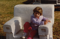 Girl sitting in Monte Ne chair at Frisco Park, 1987.png
