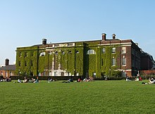 Massive, rectangular, three-storey brick building, covered in ivy. People are sitting in groups on the large front lawn.