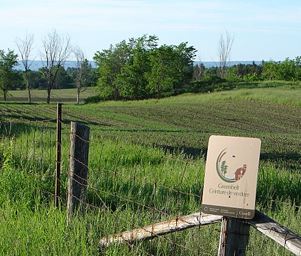 A sign that marks the Ottawa Greenbelt, an initiative that aims to protect the surrounding farmland, and limit urban sprawl Greenbelt Ottawa.jpg