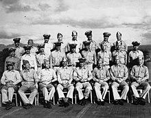 Vinte e oito marinheiros no uniforme da Marinha dos Estados Unidos colocam no convés de uma Guerra Mundial II da era do porta-aviões.