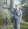 Håndkolorert dias. Portrett av forfatteren Olav Duun. Duun står foran et blomsterbed og i hånden holder han en pipe. (9469047607).jpg