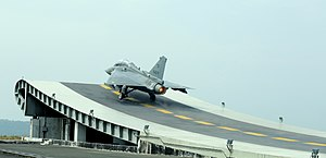Vikrant-class aircraft carrier - Naval variant of Tejas taking-off during test-flight from a shore-based ski-jump facility at INS Hansa, Goa