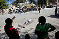 Haitian look at a body pulled out from the rubbles of a school (12 january 2010).jpg