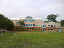 A beige building with a large windowed rotunda stands before a large lawn. The sky is overcast.