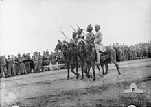 In a black and white photograph, four men with swords raised at 45 degrees wearing military uniforms and turbans ride on dark-coloured horses facing left. Behind the men, a large crowd of soldiers look on.