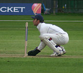 A wicketkeeper, side on, kneeling very closely behind the stumps, awaiting a delivery.