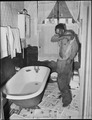 John R. Blaney, coal leader, undresses to take his bath. His is the only bathroom in ... camp. He has been with... - NARA - 540937.tif