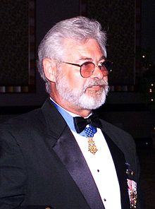 Head and shoulders of a man with gray hair, a full gray beard, and tinted glasses in a tuxedo. A medal, hanging from a blue ribbon around his neck, sits just below his bow tie.