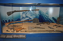 Photograph of preserved musket stocks and other remains of firearms in a display case