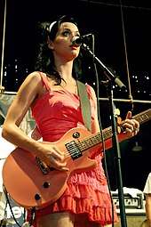 A woman in a pink dress playing her guitar in front of a microphone