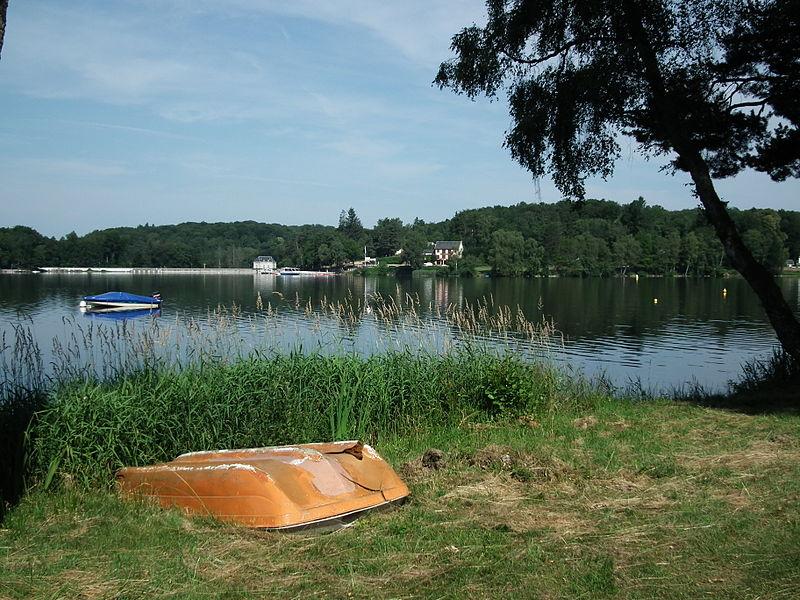 Le lac des Settons sur la rive gauche, vu sur une vieille barque au premier plan et sur le barrage à l'arrière plan.