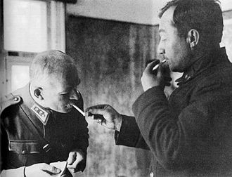 Karl Lennart Oesch - Soviet division commander Vladimir Kirpichnikov as prisoner of war in 1941 lights a cigarette for Oesch. Kirpitsnikov was caught inside a pocket (motti) during the Finnish reconquest of the Karelian Isthmus.