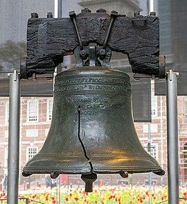на почерневшем деревянном коромысле свисает большой бронзовый колокол с ярко выраженной трещиной.  Это Колокол Свободы