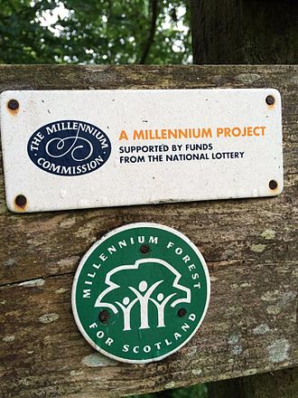 Millennium Forest for Scotland - Logo for the project (green), below the logo of The Millennium Commission seen here on a signpost at Mugdock Country Park.