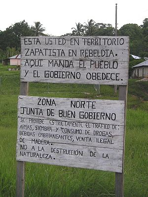 "Zapatista Army of National Liberation - Federal Highway 307, Chiapas. The top sign reads, in Spanish, ""You are in Zapatista rebel territory. Here the people command and the government obeys."" Bottom sign: ""North Zone. Council of Good Government. Trafficking in weapons, planting of drugs, drug use, alcoholic beverages, and illegal selling of wood are strictly prohibited. No to the destruction of nature."""