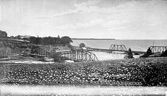 Sydney and Louisburg Railway - ca. 1900-1925 A view of the road (nearer) and Sydney and Louisburg Railway (further) bridges at the mouth of the Mira River at Mira Gut. Both bridges had swing spans to allow vessels to travel up the Mira River. After the railway shut down the nearer bridge was demolished and the further bridge was converted to carry the road.