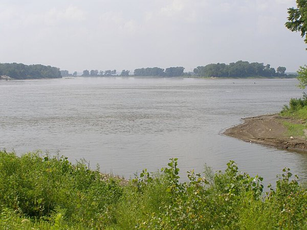 The Missouri River (center) joins with the Upper Mississippi River (right), more than doubling the flow south (left). Wood River, Illinois is in the foreground. Missouri River joins the Mississippi River.JPG
