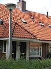 foto van Blok met 8 woningen, gecombineerde toegangen van twee woningen onder een ingestoken schilddak, zijkant met houten topgevel, aan oostkant en westkant toegangspoorten tot binnenterrein, onderdeel van complex bejaardenwoningen in Tuindorp Nieuwendam