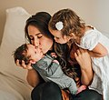 Mother with children kissing baby.jpg