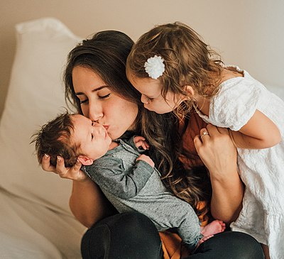Opioids and oxytocin are neurochemicals that support the mother-child bond in humans and other mammals. Mother with children kissing baby.jpg