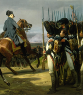 Napoleon, on a horse, looks across a line of bearskinned-hatted troops, one of the soldiers is breaking ranks and holding his hat up gesturing towards Napoleon