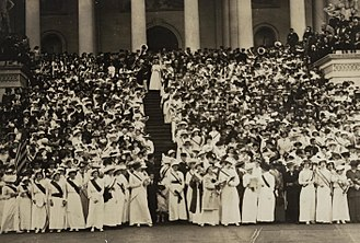 """The March of the Women - Congressional Union for Woman Suffrage petitioners on the steps of the United States Capitol, 9 May 1914. Those in the front line are singing """"The March of the Women""""."""