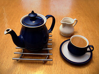 Tea in the United Kingdom - A ceramic teapot on a metal trivet, a cream jug, and a full teacup on a saucer