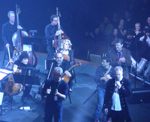 A small orchestra mostly compromising of the string section is playing on stage, with one person holding a microphone and the audience are on the topright of the picture.