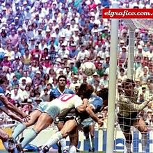 Photographie en couleurs. Un joueur anglais et un joueur argentin se jettent presque à l'horizontale vers le ballon qui file vers les buts laissés vides par le gardien argentin, en retard.