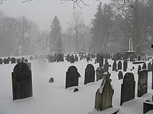 Gravestones on a cloudy and snowy day