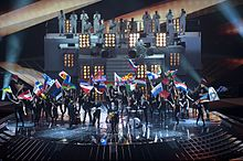 Photograph of the opening act during the 2011 contest; Stefan Raab performs with a band while multiple women dressed as Lena dance behind them while waving the flags of the participating countries