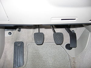 Footstool - Automobile pedals in a Subaru Legacy. From left to right: foot rest, clutch, brake, accelerator.