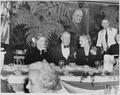 Photograph of movie stars Diana Lynn and Alexis Smith, seated at a table with an unidentified man during the... - NARA - 199326.tif