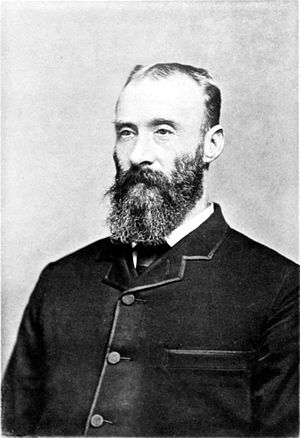 Black and white photograph of a man with a dark beard, wearing a dark jacket.