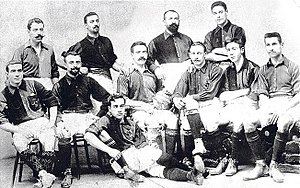 Sepia picture. 11 men pose for a squad picture, half of them bearded. Some sit on chairs, some stand and one is lying on the floor