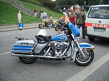 A Harley-Davidson motorbike in blue and silver, with a helmet on the seat.