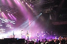 "A wide shot of a stage with four musicians visible: each is playing a type of guitar. A drum kit is mid-stage but the drummer is obscured by lighting and equipment. The audience are across the front, below the stage, some have one fist raised. A photographer is centred, front of stage, another is further to the right with a camera pointing at the band, a third cameraman is  left pointing into the crowd. Behind the group on the left is a large screen which depicts various words including ""Fight clouds baby blue despair skin red lies lost stars ith empty rocket paint love g"". Overhead lights shine down on the performers. To the right is a large sign with white writing ""bring your living room to life"" on red-orange background."