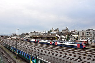 Rapperswil railway station - Railway station area, Schloss Rapperswil and St. John's Church to the right, Seedamm and railway station building in the background (to the left)